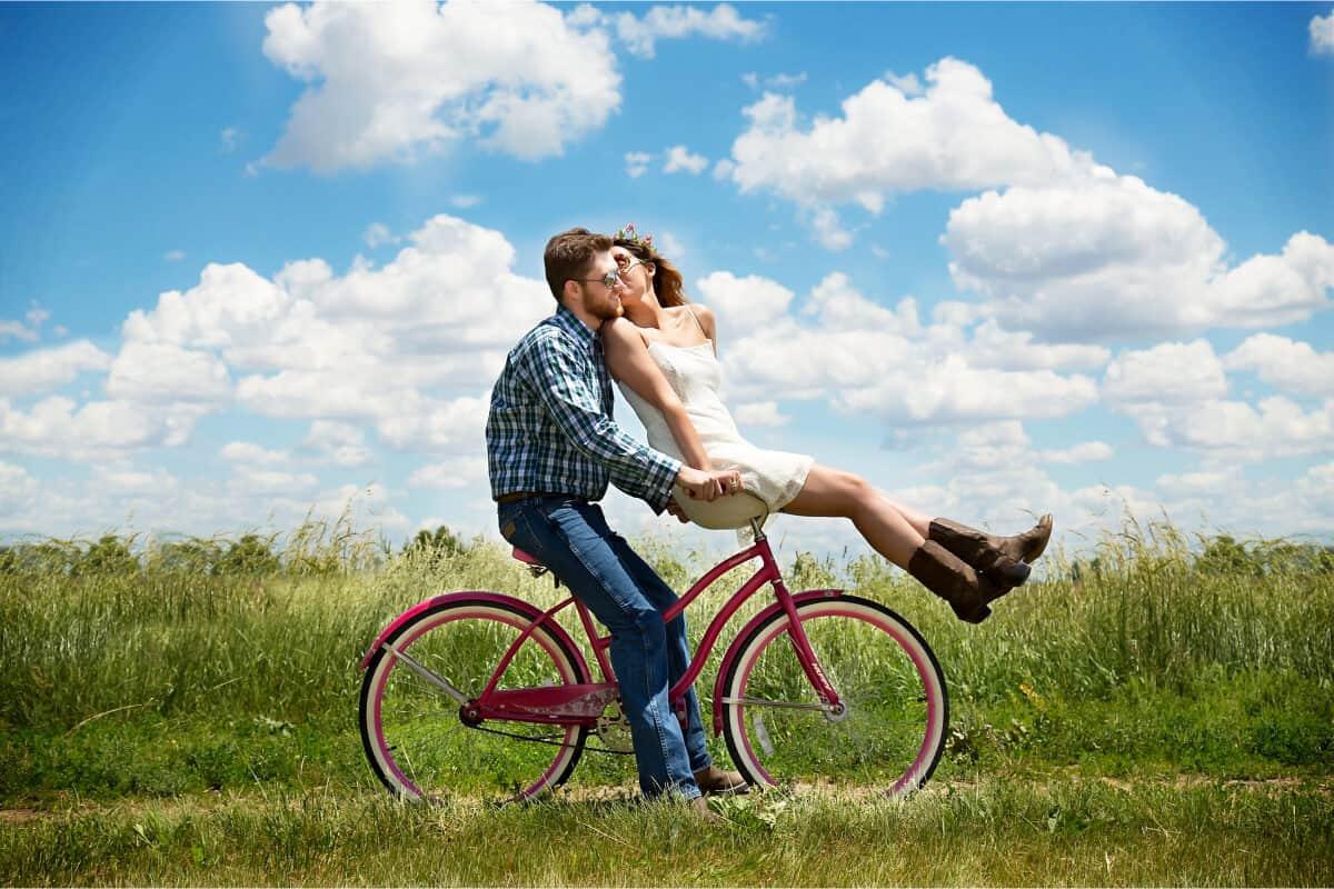 pareja montada en bici y dandose un beso